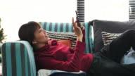 Frau auf dem Sofa liegend und mit Telefon