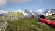 A woman lying down to relax on top of peak while hiking the French Alps.