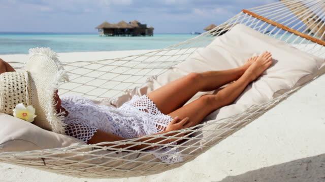 Woman lying in hammock near the sea.