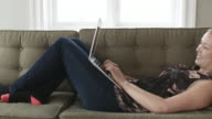 Woman lying on a couch working on a laptop