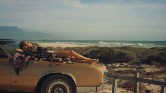 Woman lying on car at the beach