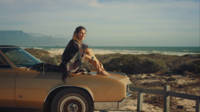 Woman lying on car at the beach