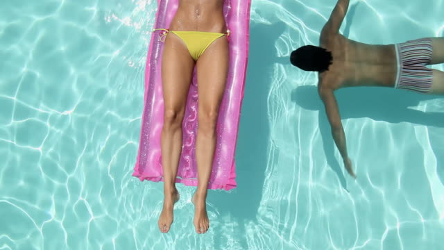 Woman lying on inflatable and man swimming underwater in pool