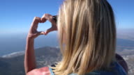 Woman makes heart shape with hand in Cape Town, South Africa