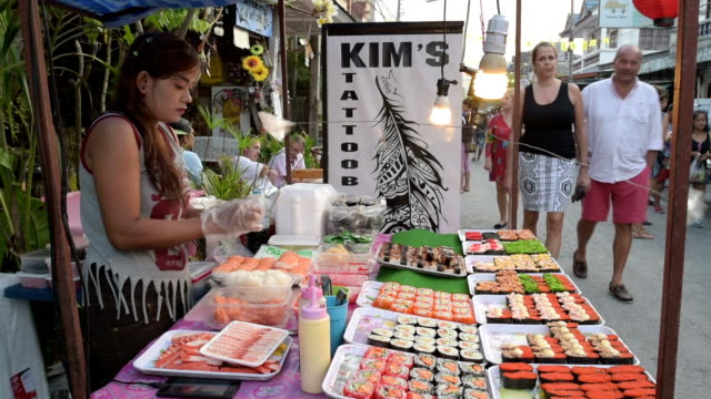 A woman makes Sushi in a food stall at night market