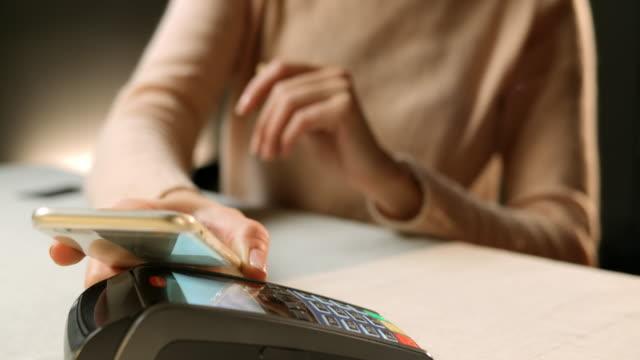 SLO MO Frau macht eine contactless payment mit Telefon
