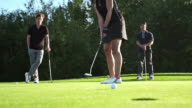 Woman making a golf putt