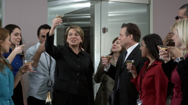 MS Woman making champagne toast to group of colleagues, Dallas, Texas, USA