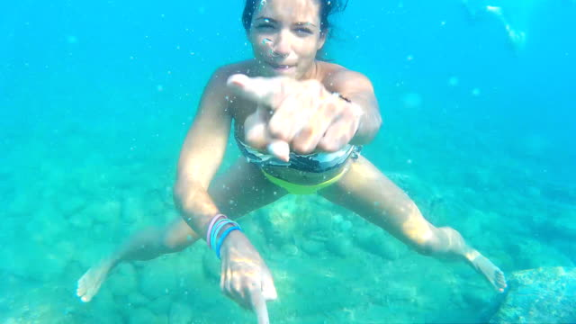 Frau machen Gesichter Unterwasser