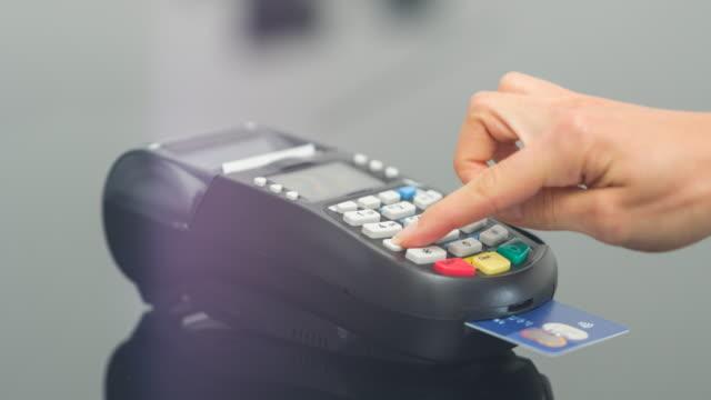 Vrouw betaalt met credit card en het invoeren van de PIN-code