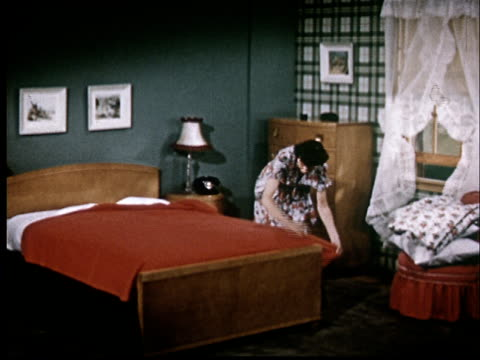 MS, Woman making up bed with red cover