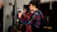 Woman Mechanic is Repairing Bike In Workshop, And Craftsman Assisting