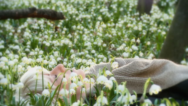 HD DOLLY: Woman Meditating Among Spring Snowflakes