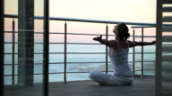 Woman meditating at sunrise