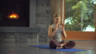 WS Woman meditating in living room, fireplace in background / Whistler, British Columbia, Canada