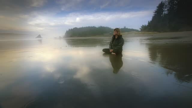WS POV ZO Woman meditating on beach / Bandon, Oregon, United States