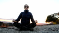 Woman Meditating on Top of Hill at Sunset