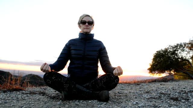 Vrouw bovenop de heuvel mediteren bij zonsondergang