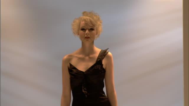 MS Woman modeling asymmetrical black dress on catwalk / London, England, UK