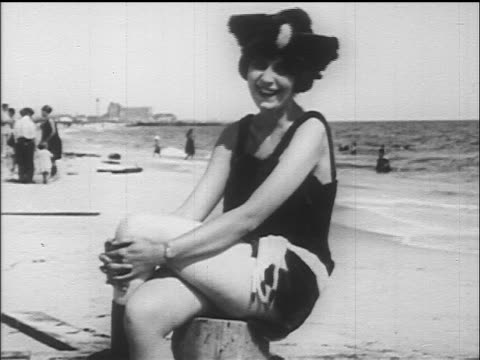 B/W 1917/18 woman modeling seal swimsuit sitting on beach + laughing