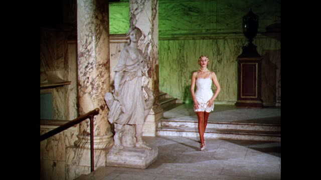 MONTAGE Woman models a broad waist corset in a marble hallway with sculpture / UK