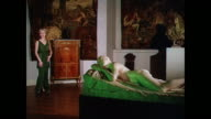 PANNING Woman models a full length dress in a gallery with a sculpture / UK