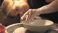 CU ZO Woman molding clay on wheel / Naperville, Illinois, USA