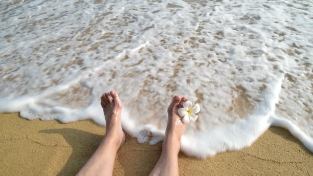 A woman moves her bare feet and toes at beach