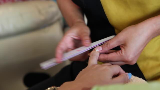 woman nail files in beauty salon
