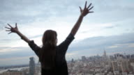 woman on a rooftop raising her arms over Manhattan