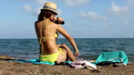 Woman on beach applying suncream on her body