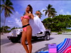Woman on beach removing shirt to reveal bikini
