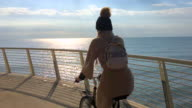 Woman on bicycle & golden sunbeams on sea