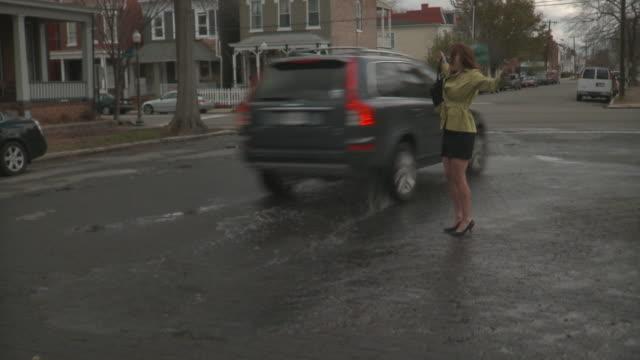 WS Woman on city street, car passing by and splashing water / Richmond, Virginia, USA