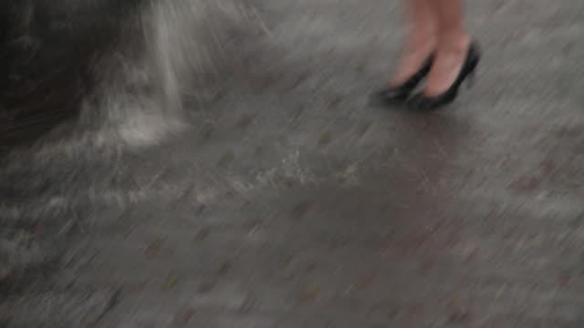 MS Woman on city street, car passing by and splashing water / Richmond, Virginia, USA