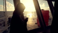 Woman on ferry boat using a smartphone