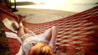 Woman on hammock looking at sunset