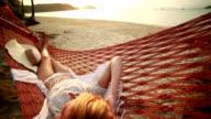 Donna guardando il tramonto su un'amaca