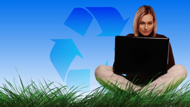 MONTAGE WS Woman on meadow with laptop and recycling symbol