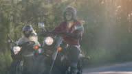 SLO MO. Woman on motorcycle waves her friend around and laughs as she speeds past her.