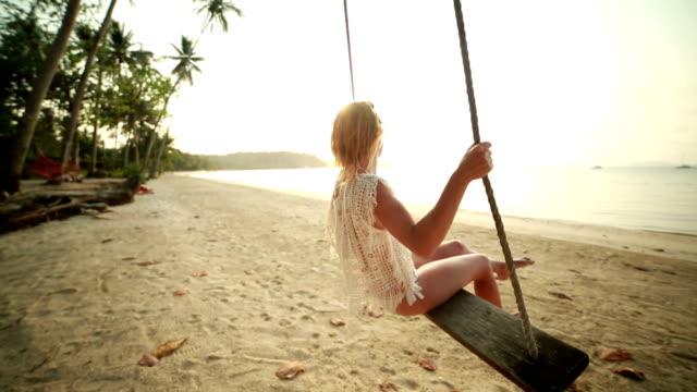 Frau auf seasaw am tropischen Strand