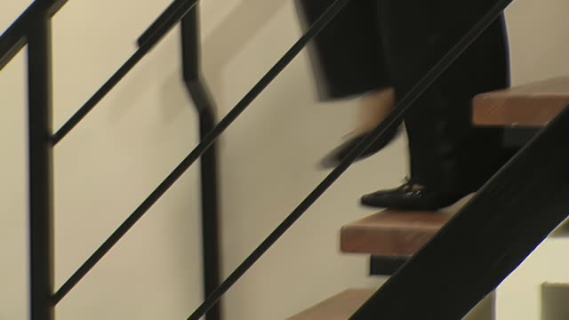 Woman on stiletto heels moves up and down on staircase