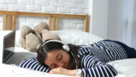 Woman on the bed listening to music with Laptop