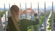 Woman on top of Arc de Triomphe forming a heart shape with hands