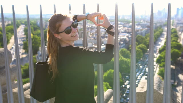 Woman on top of Arc de Triomphe in Paris looking down at the city, forming a heart shape with hands
