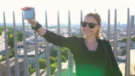 Woman on top of Arc de Triomphe in Paris taking selfies
