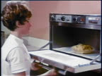 1969 woman opening oven + taking out casserole / turns to camera + smiles / industrial