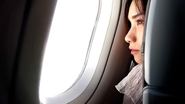 Woman opening the blind and Looking Outside of Airplane Window