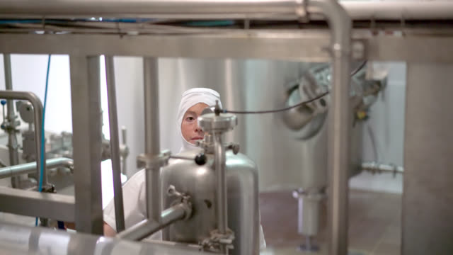Woman operating a machine at a dairy factory