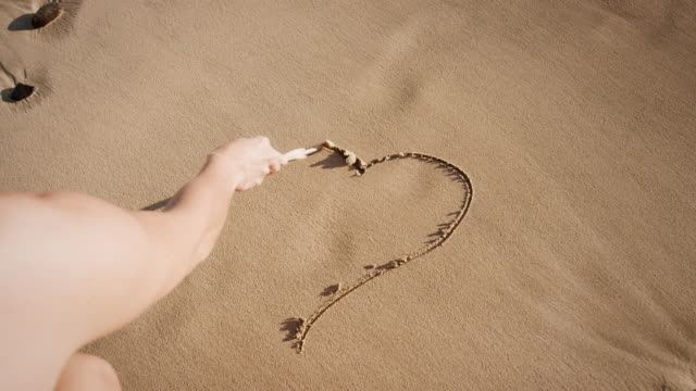 Woman painting heart shape in sand